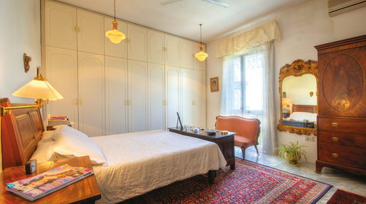 What was once a terrazzo has been converted to a spacious Master Bedroom that looks over the garden from a small balcony. An intricately carved Victorian coffer stands at the foot of the bed. © Alan Carville