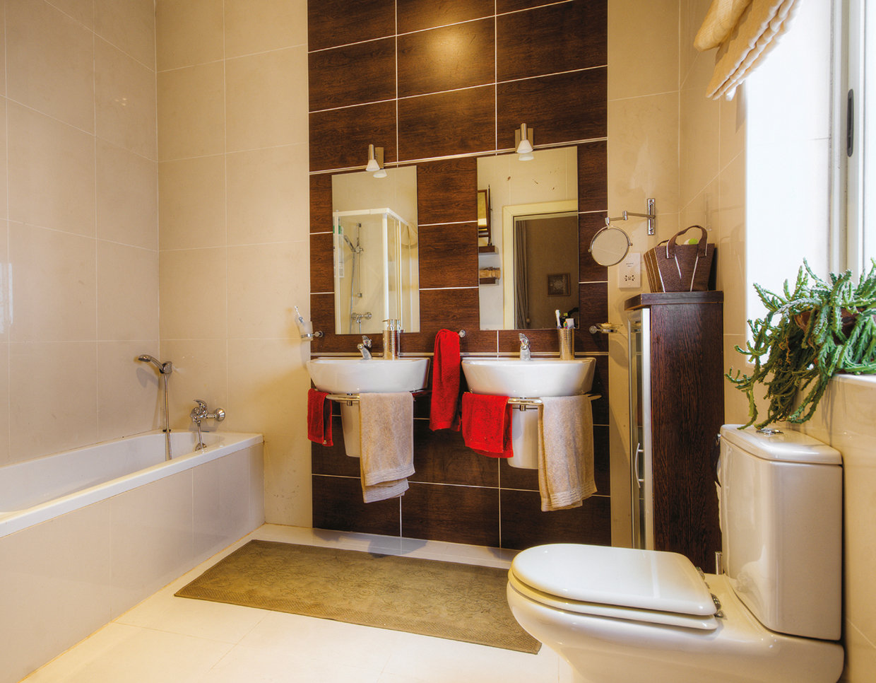 The bathroom is all-modern with Travertine marble walls and white fittings. © Alan Carville