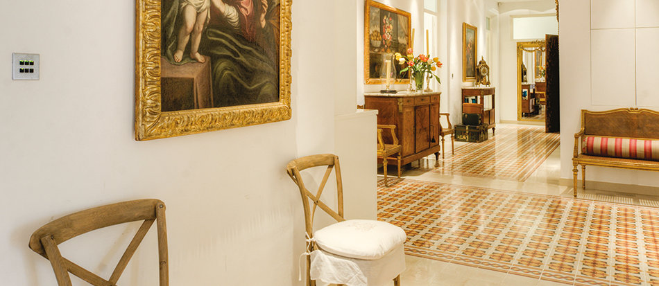 A pair of modern bentwood chairs flank an Italian painting of The Virgin and Child. The baroque coloured glass chandelier draws the eye towards the tall mirror at the end of the hallway, lengthening the view further. © Alan Carville