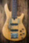 old bass guitar on wooden background.jpg