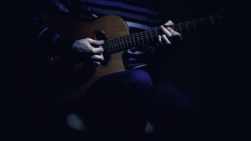 Musician and his gypsy guitar in dark bl