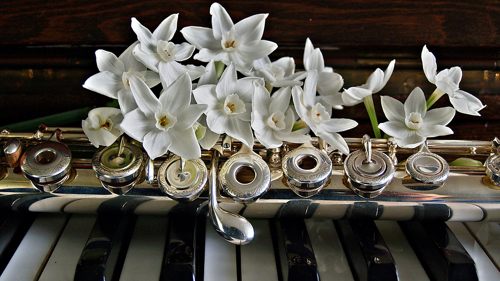 The middle of a flute on top of piano keys with white flowers on the flute.