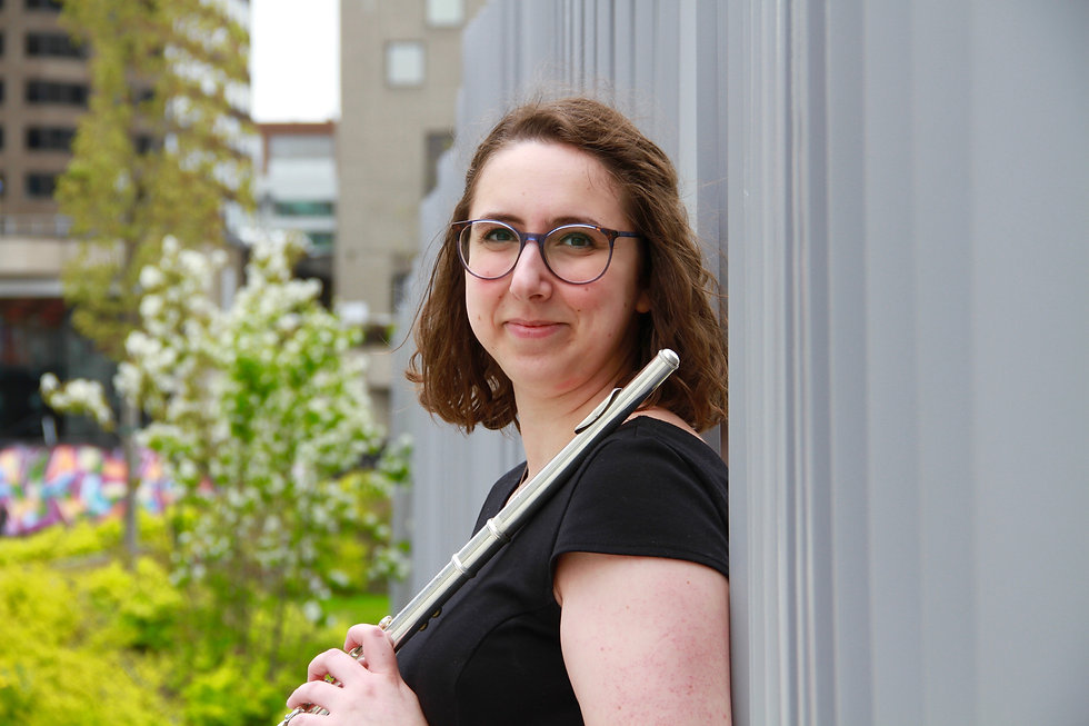 Caitlin smiling at the camera in a black dress, holding her flute, in front of a grey building.