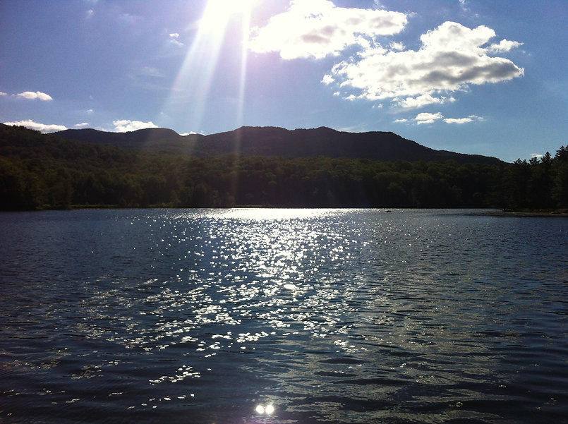 Landscape view of a shiny lake, mountains in the background, blue sky above.