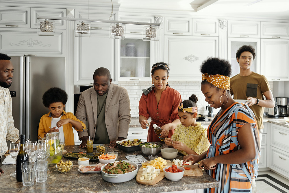 Black family with two young kids, a teenager, and four adults prepare dinner together.
