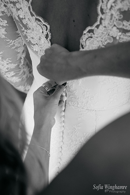 The wedding dress being buttoned up