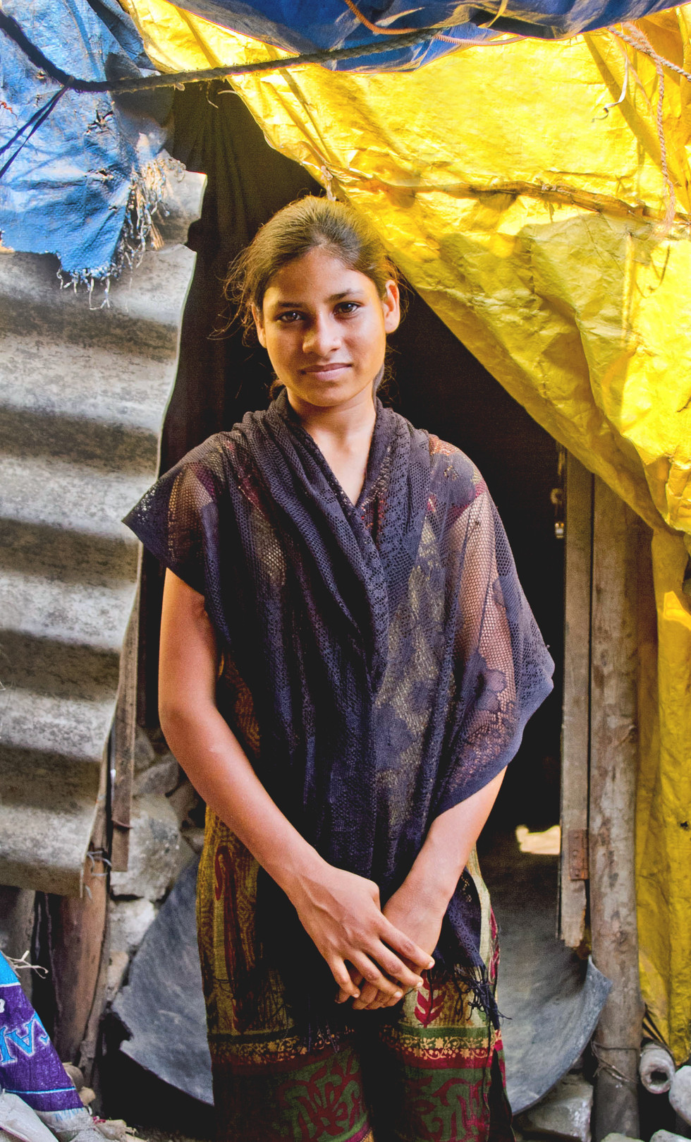 IMAGE I. MILLENNIAL GENERATION. A young teenage girl stands in front of her home, with dignity and grace. The Millennial generation of young people in the developing world, view the future with optimism and creativity. When speaking with the younger generation, its extremely clear how different they view the world and a brighter future for their community. I'm encouraged they will be the positive change, a new voice.