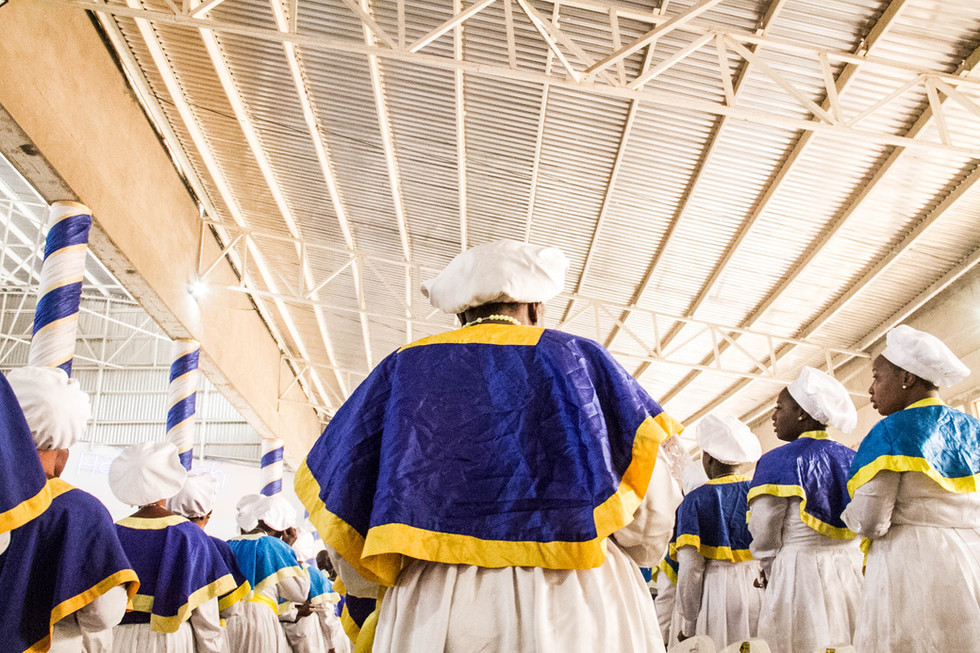 Singing hymns is a critical part of the religion, women depicted in song at the top of the sanctuary overlooking the massive crowd.