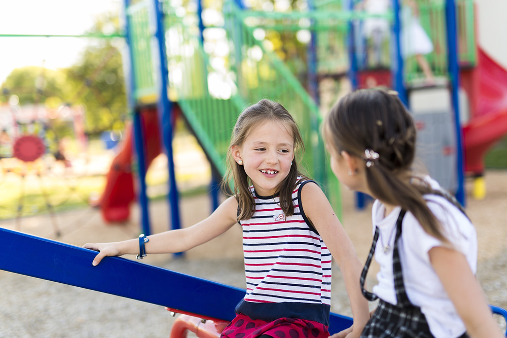 This is a picture of two caucasian girls sitting together by a playground. Both girls have long, straight brown hair, and they are looking at each other. The girl on the left is wearing a red, white and blue striped tank top, as well as a red skirt with navy blue polka dots. Her face can be seen. The girl on the right is wearing a white, short-sleeved shirt with a plaid pinafore. In the background is a jungle gym that is colored blue, green, red, black, and gray.