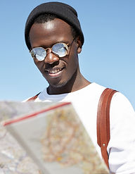 handsome-and-fashionable-young-black-tourist-in-round-shades-and-headwear-looking-at-paper