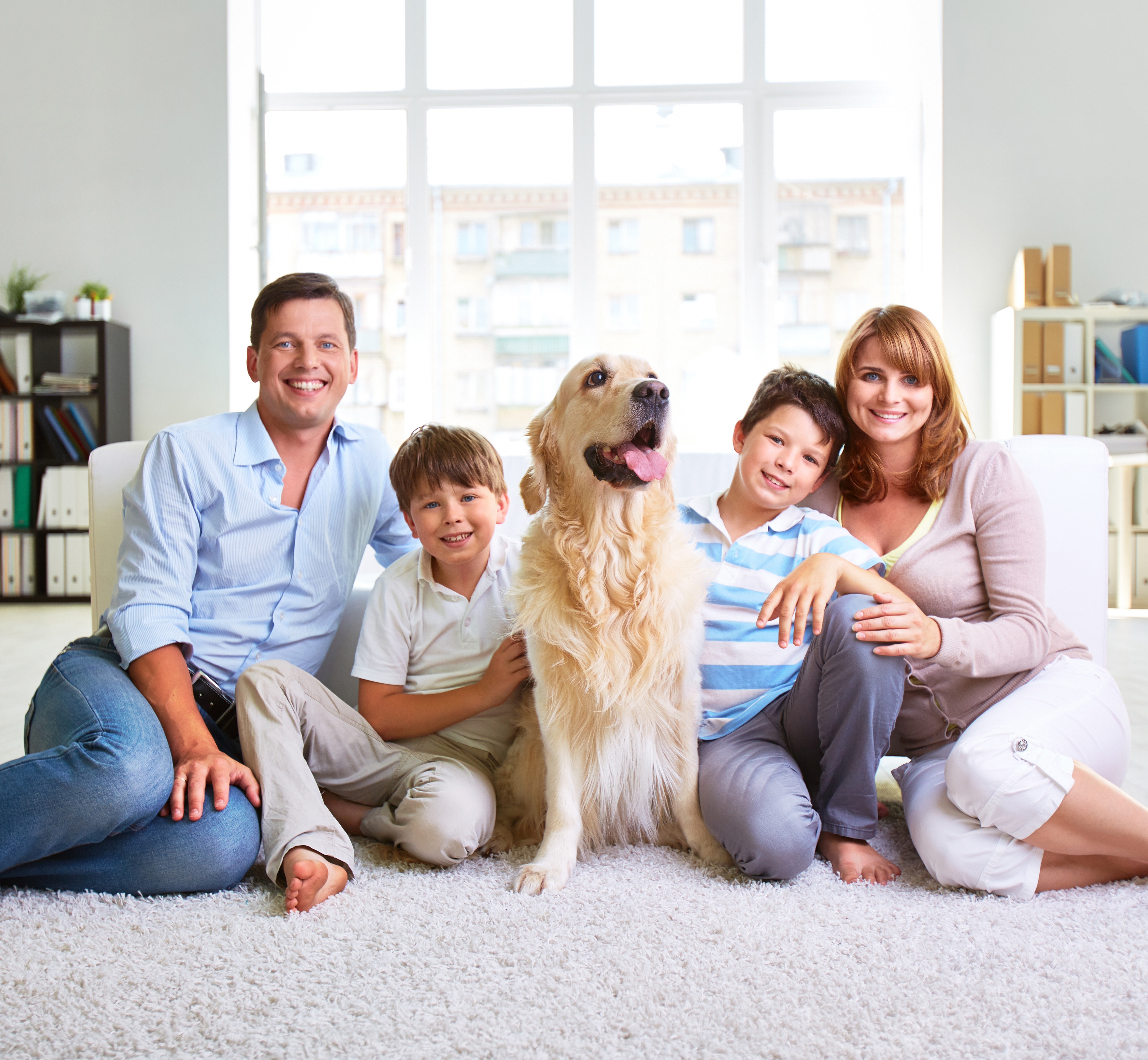 Family of four sitting on carpet