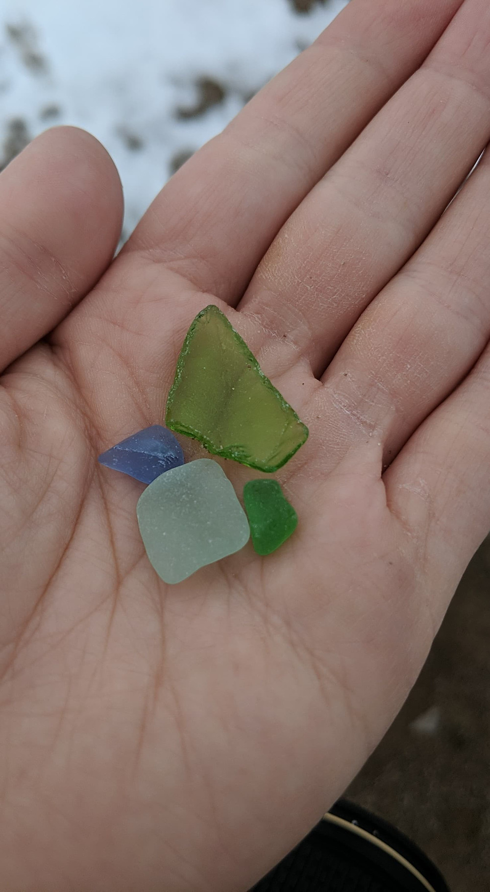 A hand holding four pieces of beach glass. One is dark blue, one is aqua, and two are green.