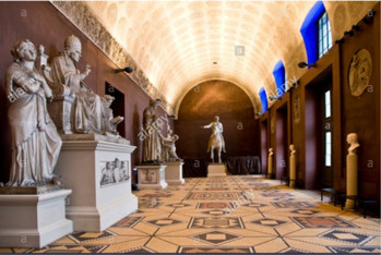 A curved surface causes more reverberation of sound than a flat surface. Here the image on the right is one of the interiors of the Thorvaldsen's museum. As you can see that this place is like a long corridor with curved ceiling. There is no furniture in the space that can absorb the sound. However there are some sculptures made of stone. The barrel vaulted curved ceiling and stone causes long reverberation period of sound.  But in such places the right kind of music should be played as the sound reverberates in an irregular pattern.