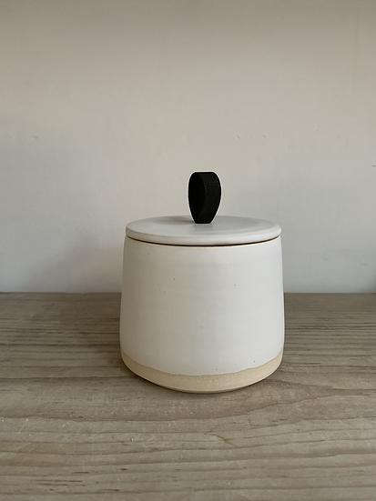 White storage jar with black handle