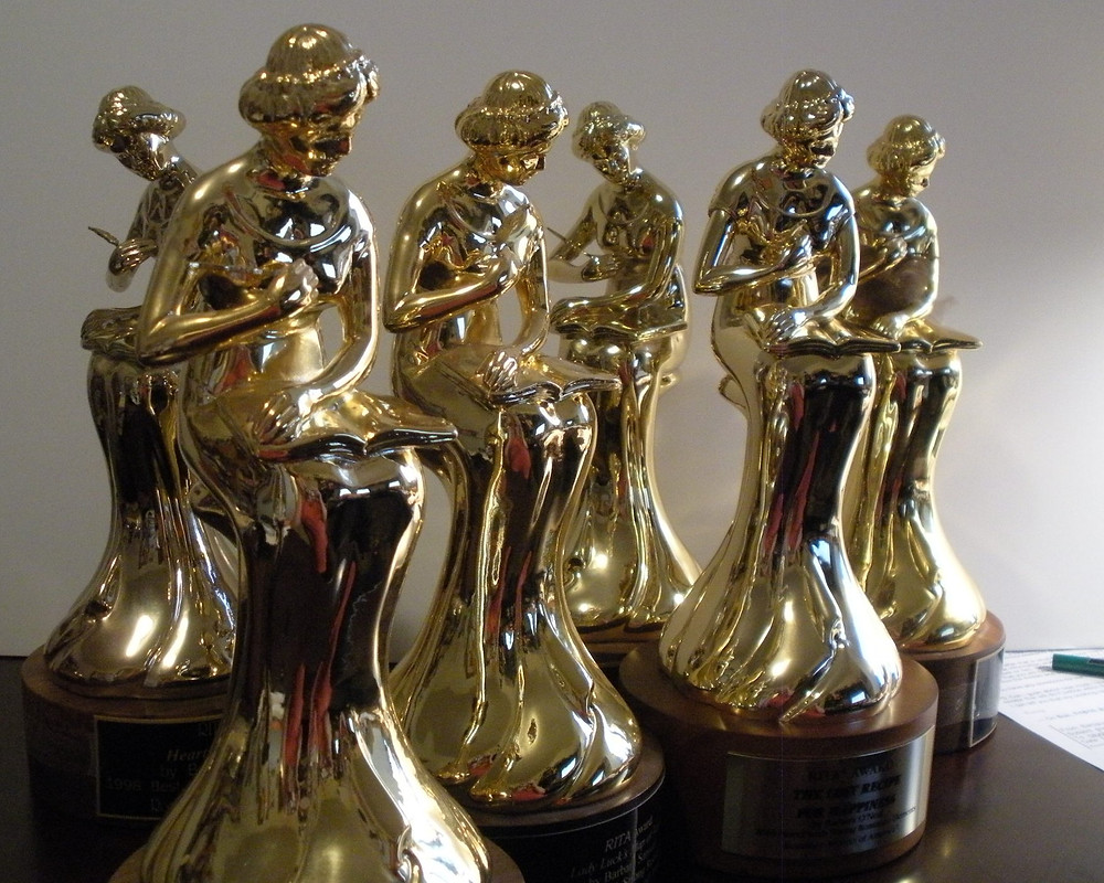 Several gold statues of a woman writing. The RITA awards