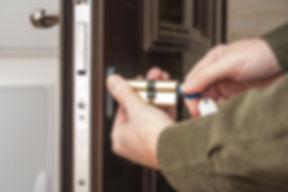 Locksmith repairing the lock on a house