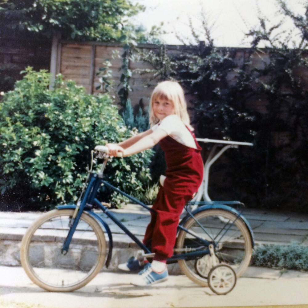 Little Abigail Willis on a bike wearing gorgeous red dungarees