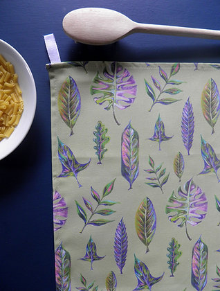 Soft green, pink, and blue leaf design on a cotton tea towel. Hand drawn by Willis Bloom and made in England.