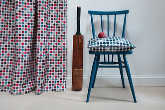 Willis Bloom Dotty about Buttons polka dot fabric. Shown as curtains in the Carnival,red, grey and blue colours. Teal blue cushion. Love pattern. Home fabric inspiration.