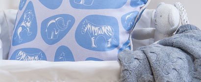 Pebble Safari fabric for childrens bedrooms by Willis Bloom. Shown as cushion in the Blue