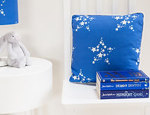 Star Bright fabric in blue for childrens bedrooms, shown in a lampshade and cushion