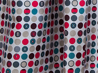 Willis Bloom Dotty about Buttons polka dot fabric. Shown as curtains in the Carnival,red, grey and blue colours.  Home fabric inspiration.