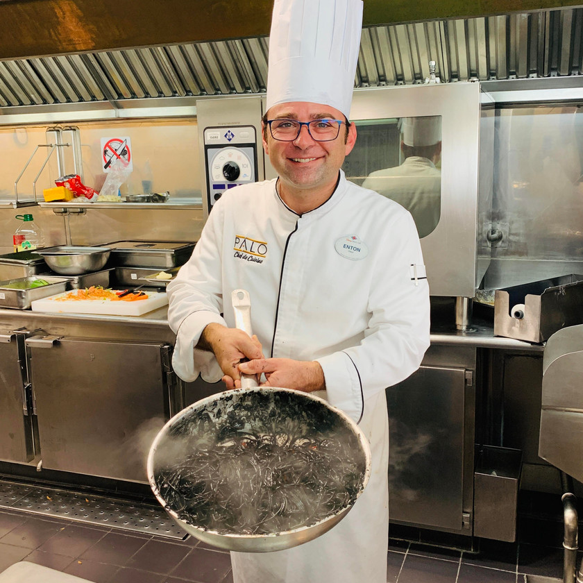 Chef toasting the black ink squid spaghetti. spaghetti al nero di seppia.