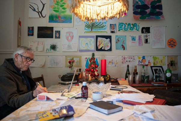 Martin Duckworth works on his dining room table in front of a wall filled with drawings, many done by his autistic daughter. His house is filled with pictures and paintings drawn notably by his seven children.