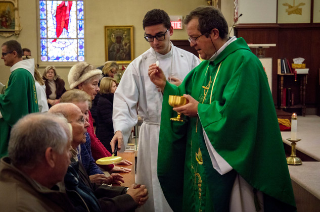 Priest Dariusz Szurko gives out the bread during Sunday mass in the Holy Trinity Parish in Pointe-Saint-Charles. Szurko came from Poland in 1987, studied in the archdiocesan seminary in Montreal and became priest in 1991. He has been serving in the Parish ever since.