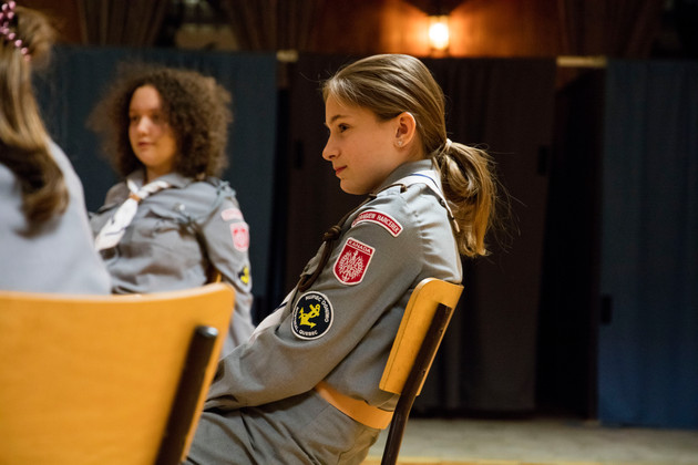 A polish girl listens to her scout leader as talks about the history of the Polish scouting movement.