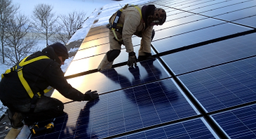 Installers work on the roof-top solar array in Waitsfield VT