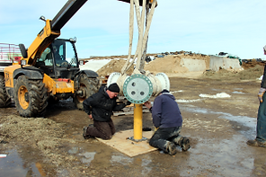 Workers drill in preparation of the wind turbine installation