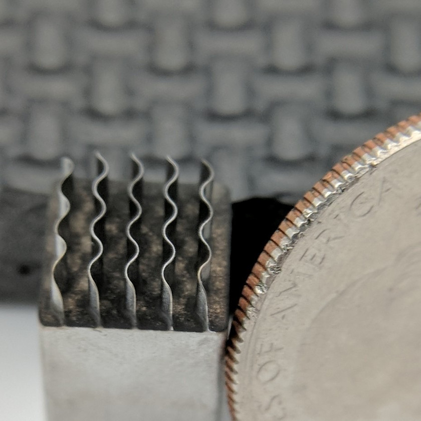 Extremely thin walls, formed via electrochemical machining, next to a quarter for comparison
