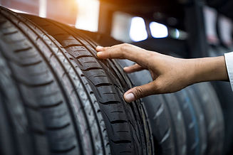 Hand checking a tyre tread