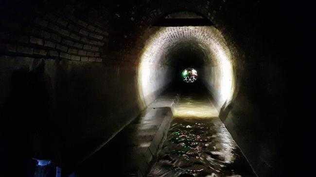 Die Kanaldrohne bei der Inspektion eines begehbaren Abwasserkanals – achszentrisch und optimal ausgeleuchtet. SaarDrones