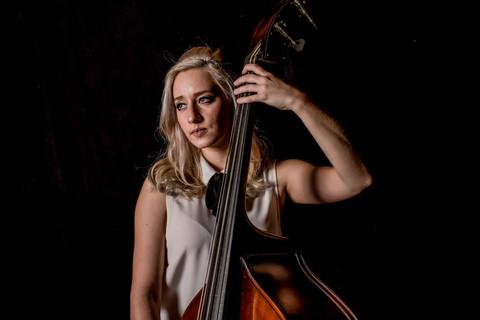 Rock 'n roll portrait photography. Rocker chick portrait. Classical musican portrait. Upright bass. Artist portrait with musical instrument. Black background. Studio photography.
