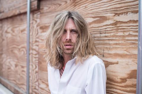 Rock 'n roll portrait photography. Blonde male portrait in front of wood background. Urban setting male model portrait.