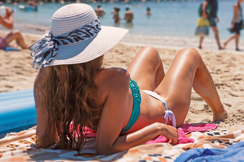girl on beach wearing hat