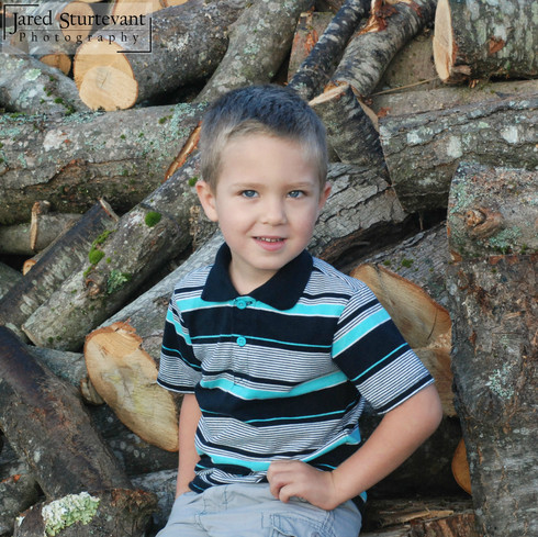 Jared Sturtevant Photography, Photograph of boy with firewood