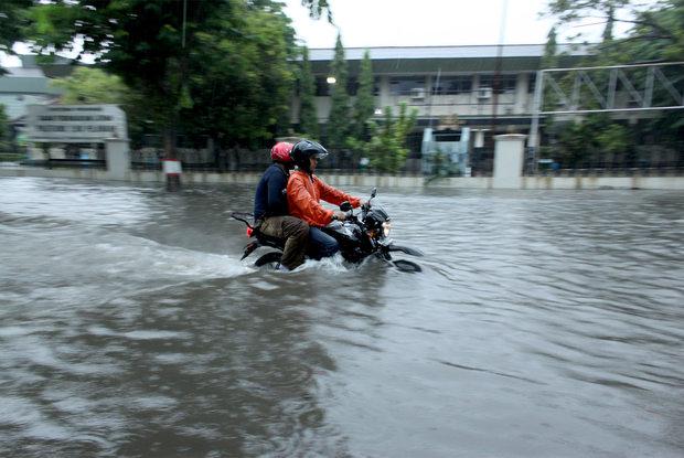 Pengendara nekat melewati Jalan Wonodro Kebun Dalem depan BPLP yang tergenang air setinggi 90 sentimeter saat hujan deras, Jumat (10/12/2010), Semarang.