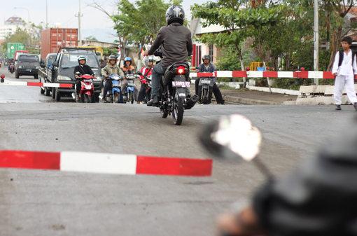 Seorang pengendara motor nekat menerobos palang pintu perlintasan kereta api di Jalan Ronggowarsito, Semarang.