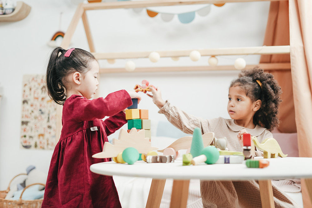 Asian girl and African American girl playing at preschool tabl with building blocks.