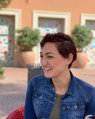 Psychologist and author of this blog smiling while sitting outside. She is wearng a denim jacket and has a short haircut.