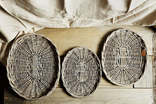multiple sizes of washed grey oval wicker trays