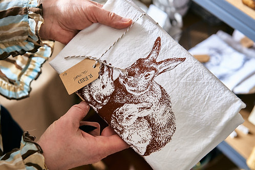 white tea towel with printed drawing of rabbits