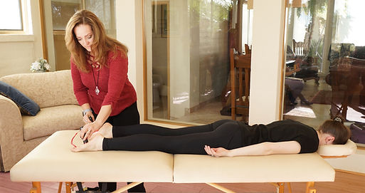 Photopuncture technician Lisa Chadsey applying photopuncture torches to a client's feet