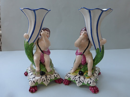 PAIR EARLY 19THC. STAFFORDSHIRE PEARLWARE PUTTOS HOLDING VASES