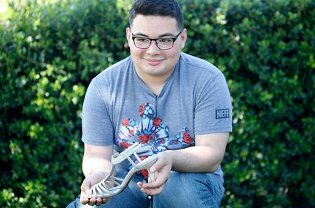 Josh DeLeon holds one of his mother's shoes he wore at the Walk a Mile in Her Shoes event. (Mya Hammond/Mosaic)