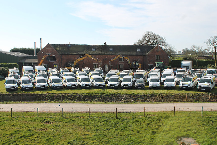 Broad Oak's fleet of vans and diggers lined up outside of the company headquarters.