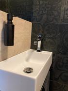 černá toaleta s dávkovačem mýdla.jpg